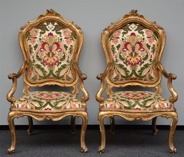 A pair of richly carved gilt wooden Rococo armchairs, probably Italy, 18thC