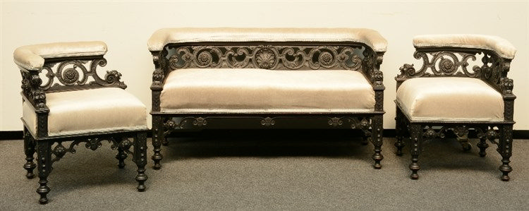 A Neoclassical ebonized sofa, richly carved, and two ditto corner chairs, H