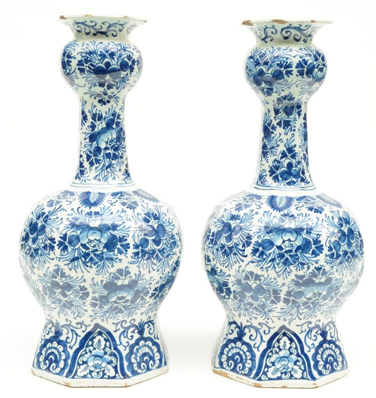 Two blue and white decorated Dutch Delftware octogonal bottle vases, marked