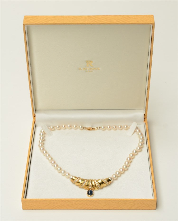A pearl necklace with an 18ct gold pendant set with brilliant cut diamonds