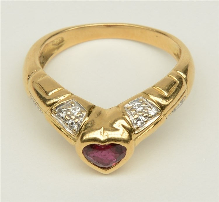 An 18ct golden ring with a heart shaped ruby and some brilliant cut diamond