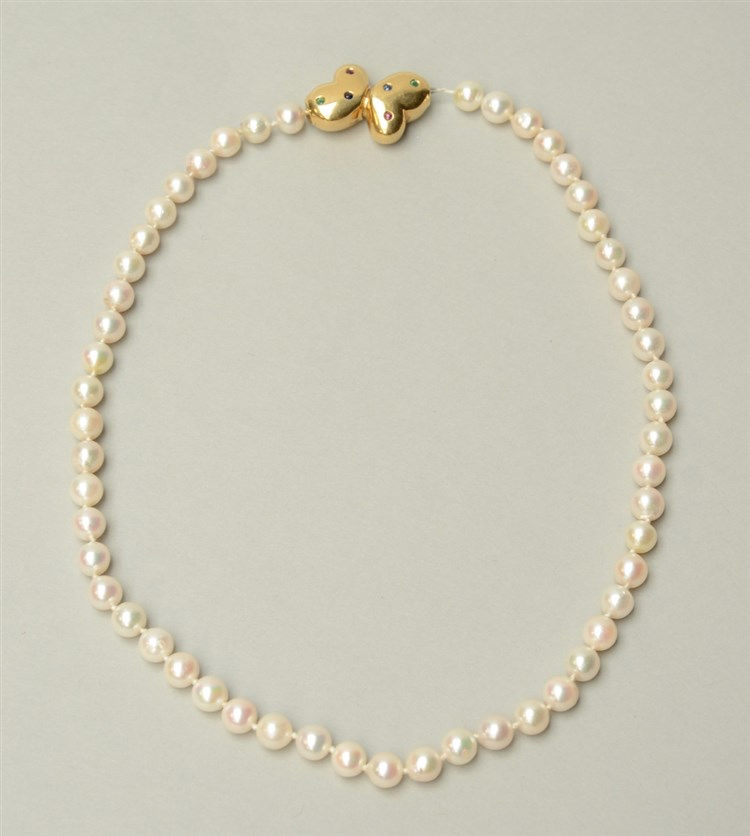 A pearl necklace with an 18ct gold extender, set with rubis, emerald and sa