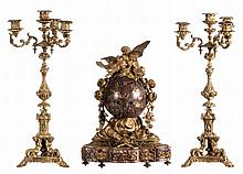 A Neoclassical red Cerfontaine marble clock with love symbolism and two accompanying bronze candlesticks in Renaissance revival style, H 39 (clock) - 47,5 cm (candlesticks)