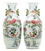 A pair of Chinese famille rose and polychrome decorated vases, one side with a rooster, a bird of prey and flower branches, one side with citrus fruit and a calligraphic text, signed, 19thC, H 59 cm