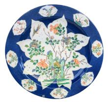 A Chinese blue poudré ground plate, the roundels famille verte decorated with a rock, flower branches and a bird, with a symbol mark, Kangxi, 18thC,H 4,5 - D 42 cm