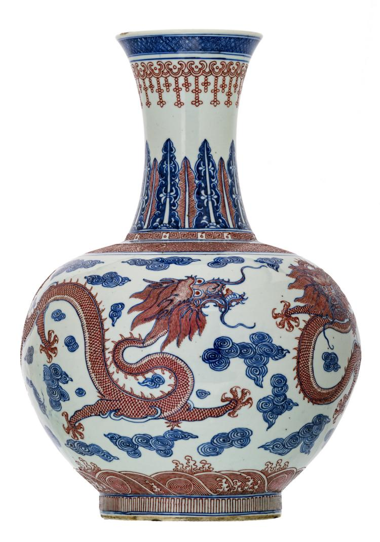 A Chinese cobalt blue underglazed and copperred glazed dragons amongst clouds decorated vase with a Qianlong mark, H 58 cm