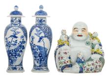 Two Chinese blue and white floral decorated baluster shaped vases and covers, the roundels with a rock, a bird and a flower branch, with a Kangxi mark; added a Chinese polychrome Budai with children, marked, H 25,5 - 33 cm