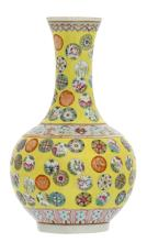 A Chinese yellow ground famille rose floral decorated bottle vase with auspicious symbols, with a Qianlong mark, H 22,5 cm
