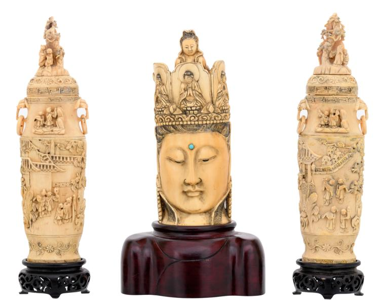 A Chinese ivory sculpture depicting the head of Buddha with a ditto coronet, partially tinted, marked, first half of the 20thC, on a matching wooden stand; added a pair of ditto vases and covers, overall carved with various animated scenes,H 19,5 - 25 (without base) - 26,5 - 28cm (with base) - Weight: 1298g
