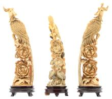 A pair of Chinese ivory sculptures depicting birds of paradise an a rock with flower branches, partially tinted, marked, about 1900, on a matching wooden stand; added a ditto sculpture depicting cranes, a rock and flower branches, H 25,5 - 29,5 (without base) - 29 - 33 cm (with base) - Weight: about 1500g