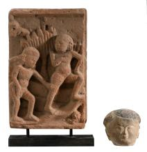 A Burmese stone bas-relief depicting two figures in a garden, on a stand; added an Oriental terracotta head with traces of polychromy, H 10 - 37,5 cm