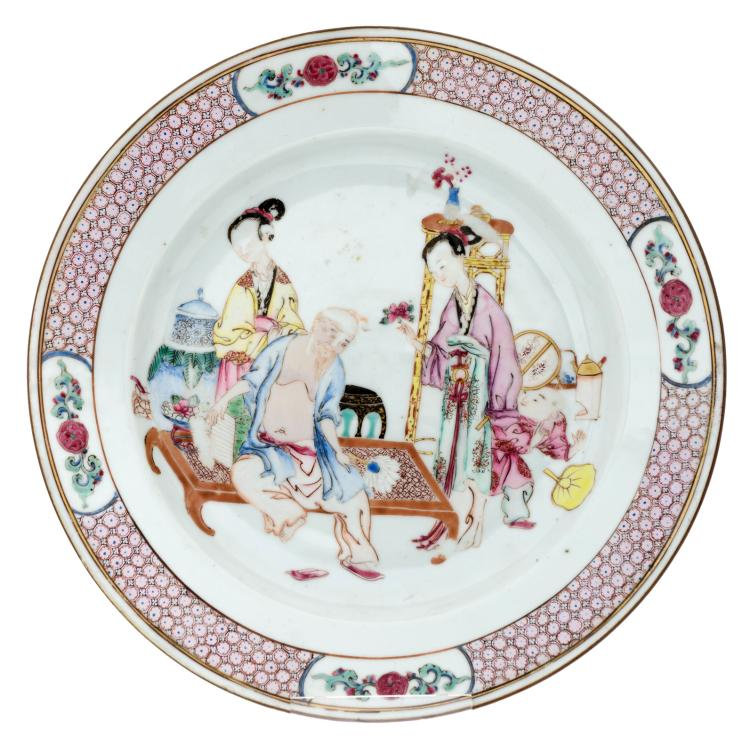A Chinese famille rose ruby back export porcelain dish decorated with a scene of two women and a young boy surrounding an elderly scholar, Yongzheng period (1723 - 1735),ø 23 cm