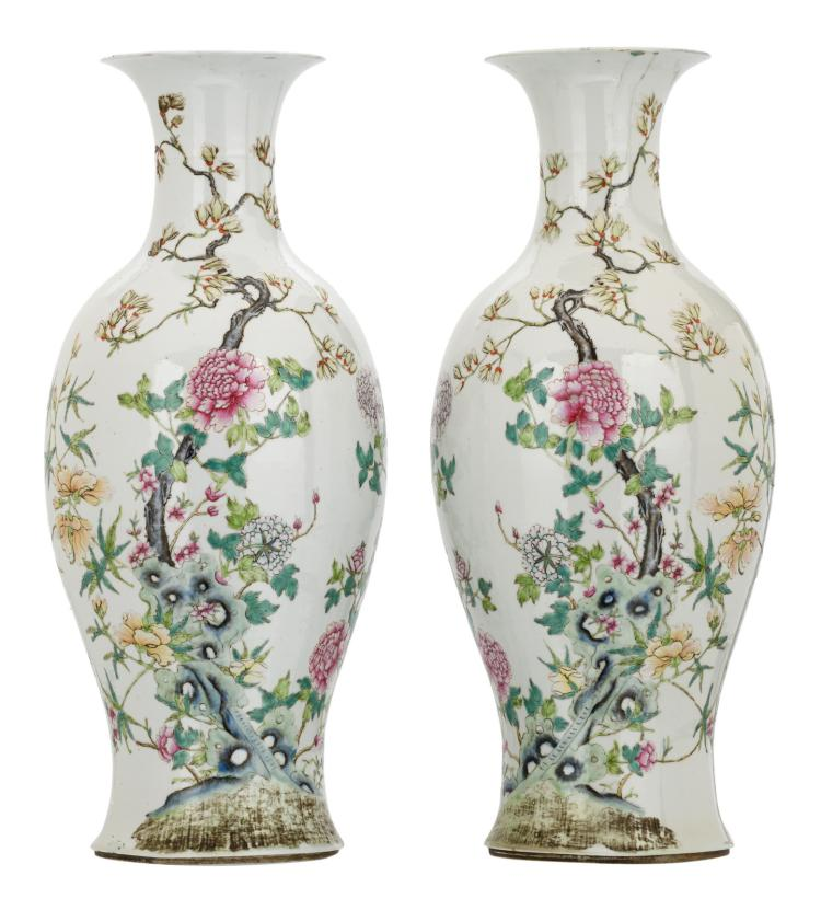 A pair of Chinese famille rose baluster shaped vases, decorated with flower branches, a rock and bats, with a Qianlong mark, H 57,5 cm