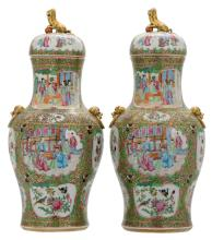 A pair of Chinese Canton famille rose floral decorated baluster shaped vases and covers, the roundels with court scenes, birds and flower branches, 19thC, H 52 cm