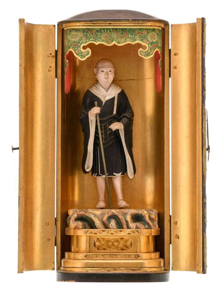 A lacquered Japanese shrine with engraved brass mounts, inside a polychrome decorated figure of a monk, Meiji and period, H 34,5 - W 14,5 - D 11 cm