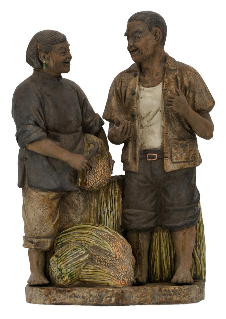 A Chinese polychrome stoneware partially glazed group depicting a peasant and his wife, marked, H 38 - W 28,5 - D 17 cm