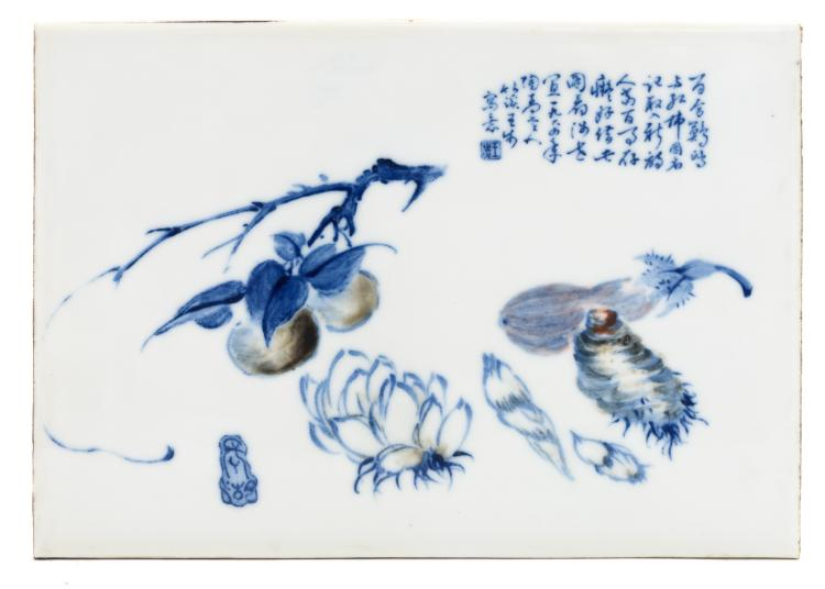 A Chinese blue and copper red underglazed decorated plaque with fruits and a calligraphic text, signed, in a wooden frame, 22 x 31 cm