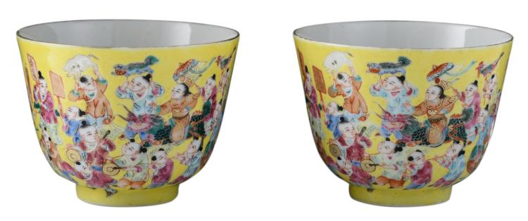 A pair of Chinese yellow ground famille rose one hundred boys decorated cups with a Qianlong mark, H 7 - ø 8,5 cm