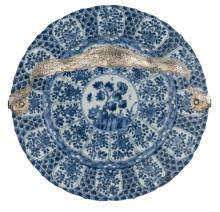 A Chinese blue and white floral decorated accolade shaped plate, Kangxi, with a Dutch silver mount (835/000), ø 27,5 cm