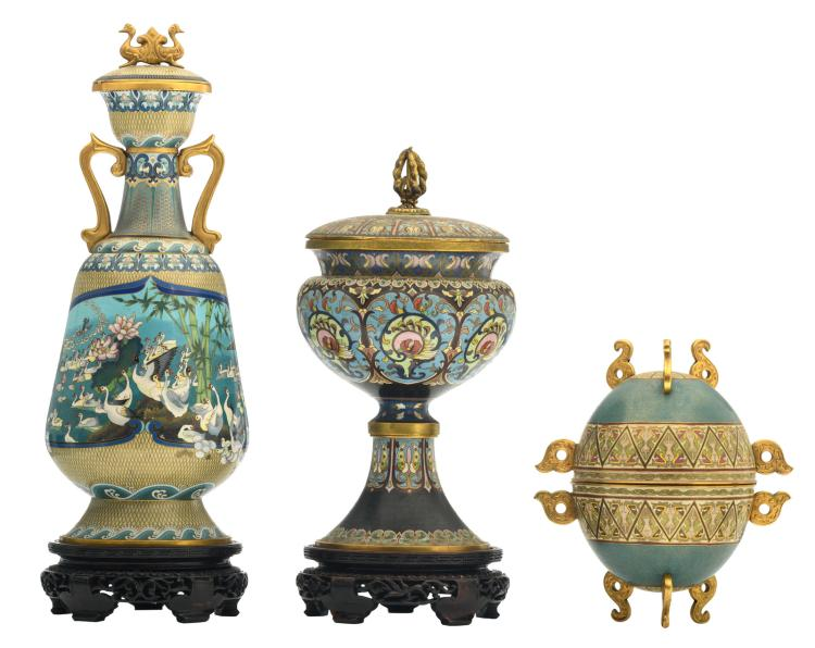 A Chinese cloisonné vase and cover and a footed bowl and cover, floral decorated, the vase with mute swans, on wooden stands; added a ditto egg shaped bowl and cover, H 26,5 - 49 cm