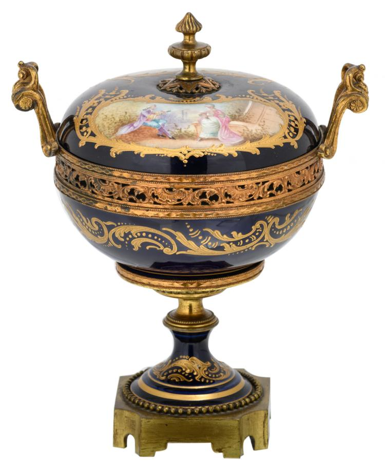 A bleu royal gold decorated pot and cover, the roundels decorated with a landscape and a gallant scene, with a Sèvres mark, H 24 cm