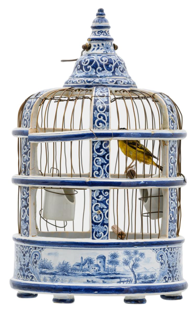 A 19thC Dutch blue and white birdcage with a stuffed goldfinch, a similar birdcage was sold at Sotheby's New York in 2011, H 41 cm