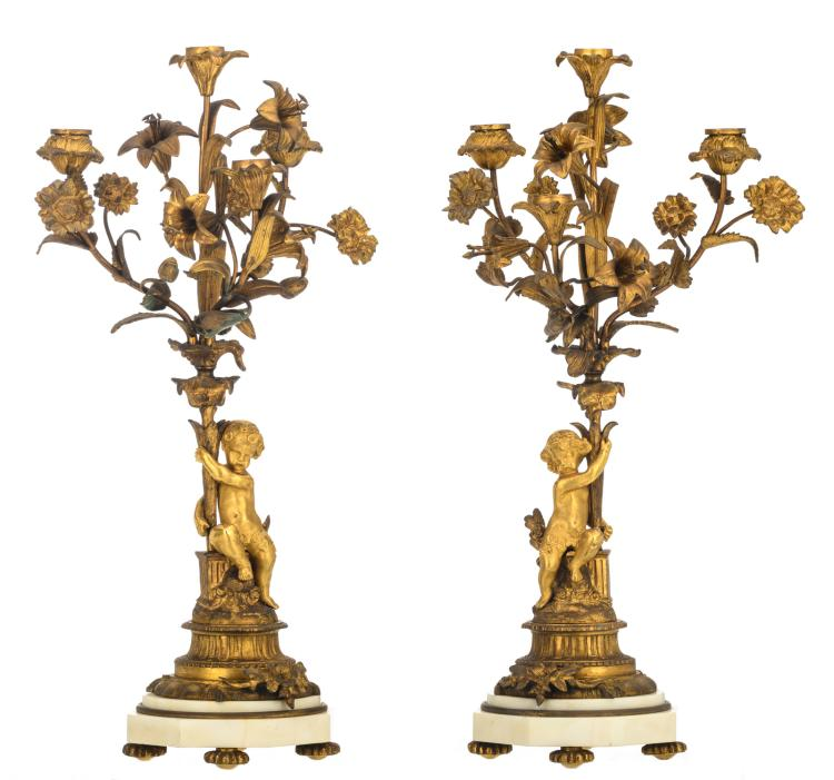 A pair of Historism gilt bronze candelabras with putti on a white marble base, H 51,5 cm