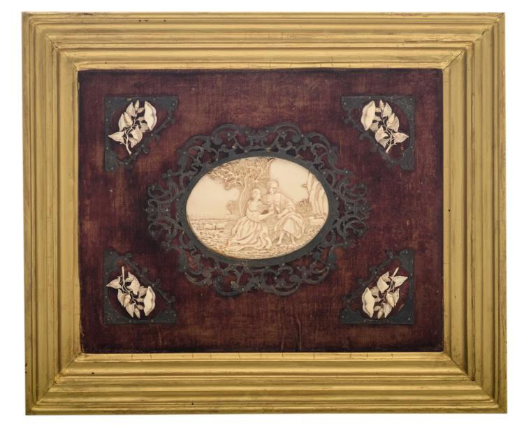 An oval ivory plaque with an allegory of love, the four corners decorated with presumably hedge bindweed, mounted in silver, last quarter of the 19thC, 24 x 30 cm