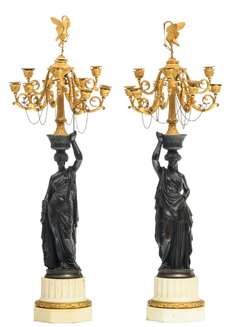 A pair of patinated and gilt bronze Historism candelabras in the form of caryatids, on a Carrara marble base, H 97 cm