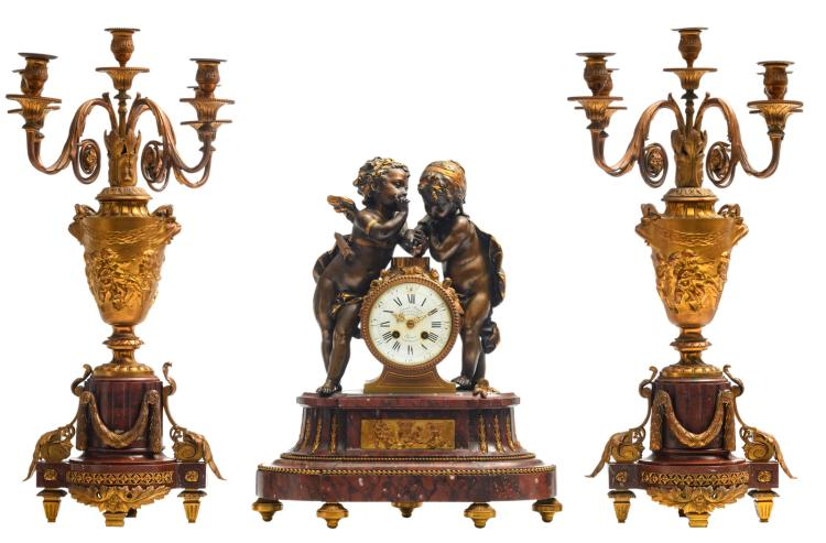 A 19thC Neoclassical gilt bronze mounted three-piece garniture on a rouge impérial marble base, the centerpiece crowned with loving amors, the work illegibly marked (Fassy Paris?), the dial signed 'Ernest Royer - Paris', H 48,5 - 65,5 cm