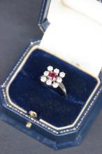 Bague en or blanc ornee d' un rubis dans un entourage de diamants