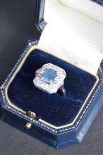 Bague en or blanc ornee d' une importante pierre bleue ??? Dans un entourage de diamants