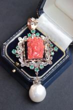 Important pendentif en or 14 K orne d' un corail rouge sculpte figurant un portrait feminin sur fond d' onyx , dans un entourage de diamants 0,55 ct et d' emeraude 1,65 ct et en pendant une perle baroque