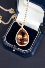 Collier en or jaune orne d' un important pendentif de citrine couleur cognac 43,9 cts dans un entourage de brillants 0,40 ct
