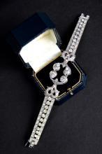 Bracelet en or blanc orne de nombreux brillants, avec motif central a decor de volutes.