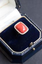 Bague en or jaune 18 K ornee d' un cabochon de corail rouge rectangulaire dans un entourage de diamants 0,20 ct