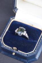 Bague en or blanc ornee d' une importante pierre verte entouree de six diamants