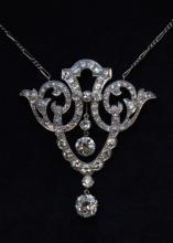 Collier en or blanc a decor de volutes ornees de brillants supportant quatre diamants en chute dont deux plus importants (de 1,2 cts et 0,70 ct environ chaque)