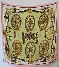 HERMES  Carré en soie imprimée à décor de roues sur un fond vert, bordure rose.