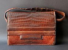INNOVATION  Sac en crocodile brun porté épaule , ouvrant par un rabat maintenu par une lanière plaquée devant