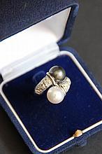 Une bague Toi et Moi en platine avec diamants d'environ 0,75 CT et perles blanche et noire.