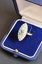 Une bague navette en or jaune 18K, pavage de diamants d'environ 1,20 CTS et émeraude d'environ 0,35 CT.