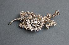 Une broche à motif de fleurs sertis de roses en argent, métal et or.