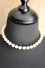Un collier de perles de culture avec fermoir en or 18K.