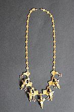 Un collier en or jaune 18K à motifs d'anges, diamants et rubis.