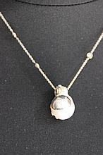 Un collier en or blanc 18K orné d'un pendentif à perle baroque et diamants d'environ 0,60 CT.