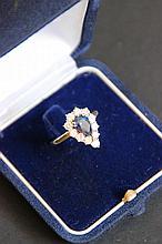 Une bague marguerite en or jaune 18K, saphir d'environ 1 CT et entourage diamants d'environ 1,10 CTS.