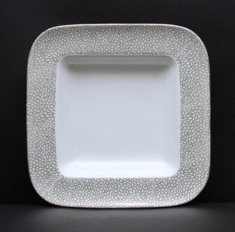 LANCEL Plat en faïence blanche à décor argenté sur le marli