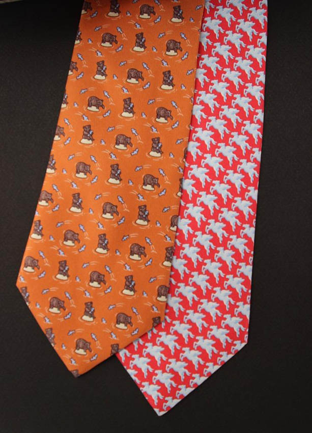 HERMES Lots de deux cravates : une rouge à motif de chevaux ailés, l'autre orange à motif d'ours et de poisson