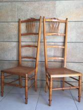 Paire de chaises de nourrice en bois mouluré à assise cannée